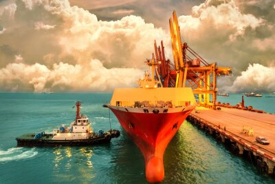 Canvas print Logistics and transportation of International Container Cargo ship with ports crane bridge in harbor and evening sky for logistic import export background and transport industry.