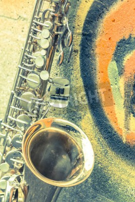 Canvas print Lone old saxophone leans against brick wall outside abandoned jazz club