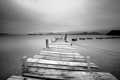 Canvas print Looking over a pier and boats, black and white