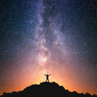 Canvas print Man and the Universe. A person is standing on the top of the hill next to the Milky Way galaxy with his hands raised to the air.