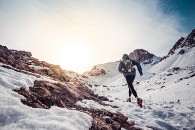 Canvas print Man running on the snow on a mountain