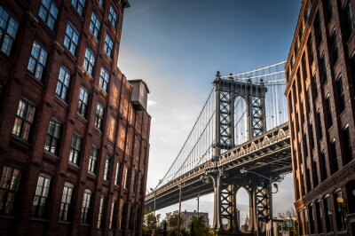 Canvas print Manhattan bridge seen from a narrow alley enclosed by two brick buildings on a sunny day in summer