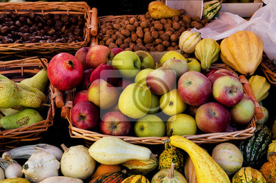 many basket of apples, pears, chestnuts, walnuts, pumpkins, fruit and vegetables on a farmer's market stall in Piedmont, Italy