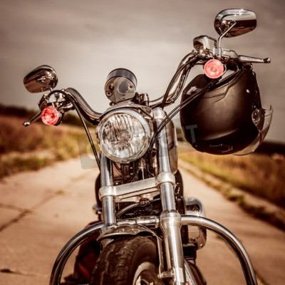 Canvas print Motorcycle on the road with a helmet on the handlebars.