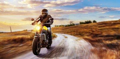Canvas print Motorrad fährt auf freier Landstrasse in den Sonnenuntergang