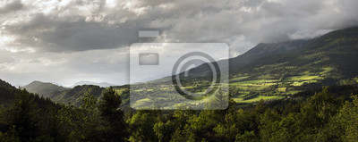 mountain landscape in low evening light with cloudy sky above village and church at the other side of valley