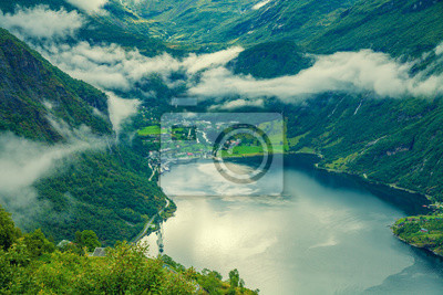 Mountain landscape with cloudy sky. Geiranger fjord in rainy weather. Wild beautiful nature Norway in evening.