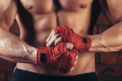 Canvas print Muscular Fighter With Red Bandages against the background of a brick wall