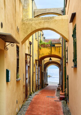 Canvas print Narrow street leading to the Mediterranean Sea in old town Varig