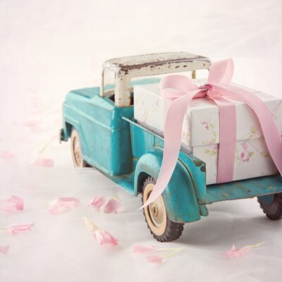 Canvas print Old antique toy truck carrying a gift box with pink ribbon