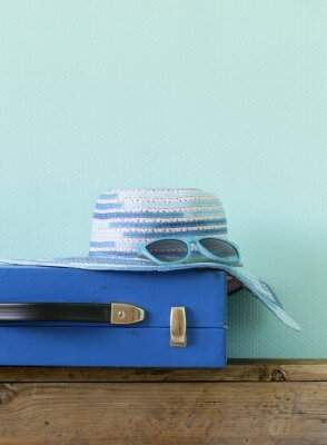 Canvas print old fashioned blue suitcase for travel and beach hat