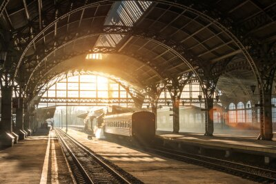Canvas print Old railway station with a train and a locomotive on the platform awaiting departure. Evening sunshine rays in smoke arches.