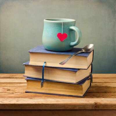 Canvas print Old vintage books and cup with heart shape on wooden table