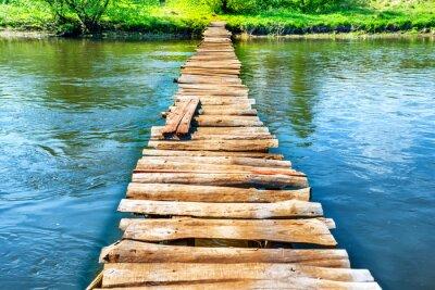 Canvas print Old wooden bridge through the river