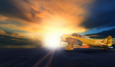 Canvas print old yellow propeller plane on airport runway with sunset sky bac