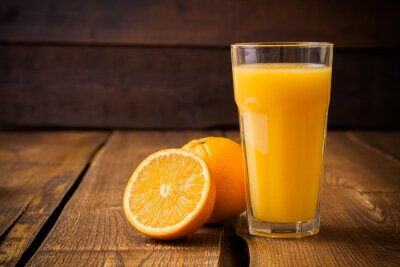 Canvas print Orange fruit and glass of juice on brown wooden background