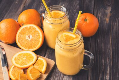 Canvas print Orange fruit smoothie in the glass jars