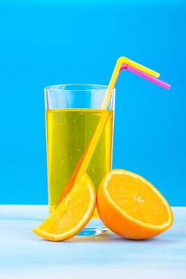 Canvas print orange juice in a glass with colored straws and orange slices on a blue background
