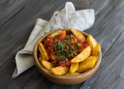 Canvas print Patatas Bravas, traditional Spanish tapas, baked potatoes with spicy tomato sauce in wooden bowl on wooden table. selective focus