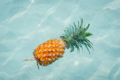 Canvas print Pineapple into water on sunny beach