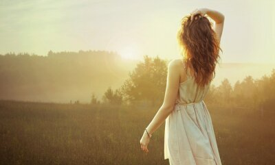 Canvas print Pretty brunette woman watching the sunset