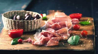 Canvas print Prosciutto with bread on a wooden board with olives