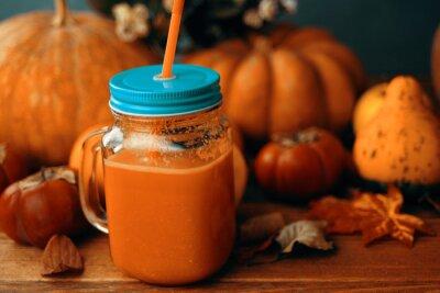 Pumpkins juice in bottles with pumpkins. Healthy pumpkin smoothie in big mugs on rustic background