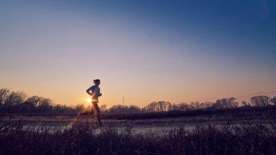 Canvas print ragazza atletica si allena all'aperto su terra di sera