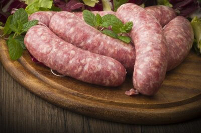 Canvas print raw homemade sausage on a wooden board