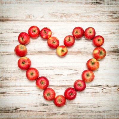 Canvas print Red apples heart wooden background. Love concept vintage