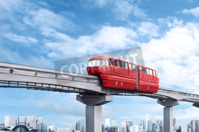 Canvas print Red monorail train against blue sky and modern city in background