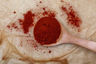 Red paprika in wooden spoon (spices collection). On rustic background.