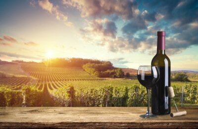 Canvas print Red wine bottle and wine glass on wodden barrel. Beautiful Tuscany background
