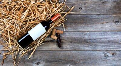 Canvas print Red wine bottle with vintage wine corkscrew on straw