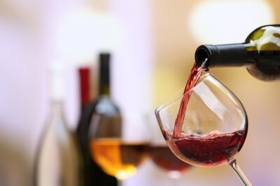 Canvas print Red wine pouring into wine glass, close-up