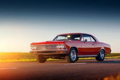 Canvas print Retro red car stay on asphalt road at sunset