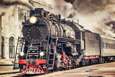 Canvas print Retro steam train departs from the station.