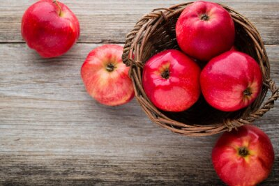 Canvas print Ripe red apples on wooden background.