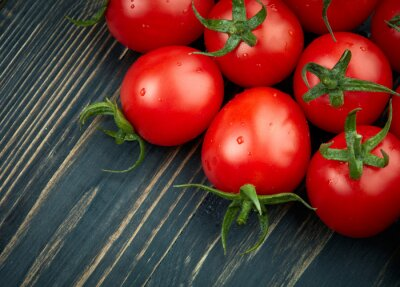 Canvas print Ripe tomatoes on dark wooden background