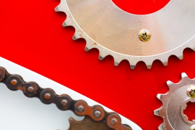 Canvas print Roller chains with sprockets for motorcycles on red background