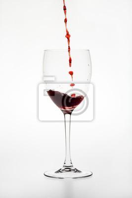 Rotwein wird vor weißem Hintergrund in ein Glas geleert