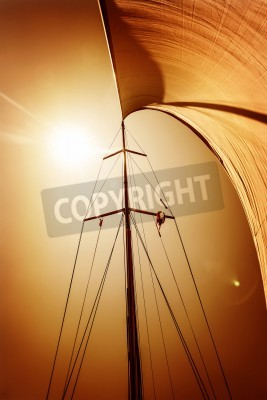 Sail fluttering in the wind on orange sky background, mild sunset light, sea cruise on luxury sailboat, summer vacation and holidays concept