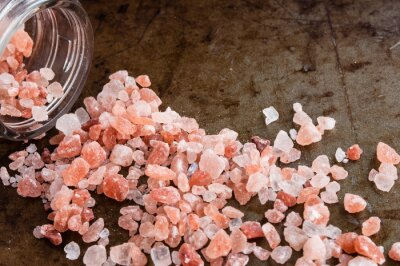 Canvas print Scattered Himalayan pink salt crystals from glass bottle on rusty metal background