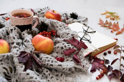 selective focus photo of grey cozy knitted scarf with cup tea and open book old wooden table. red apples, leaves, berries, autumn harvest, cozy background. time for reading books and self-development