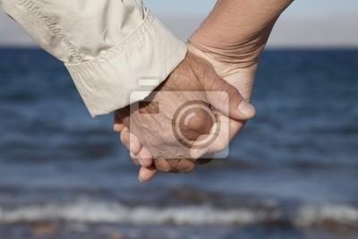 Canvas print Senior couple holding hands on the beach