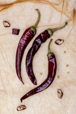 Set of dried red chillies (whole and cut) (spices collection). On rustic background.