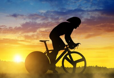 Canvas print Silhouette of a cyclist on a road racing bike at sunset.