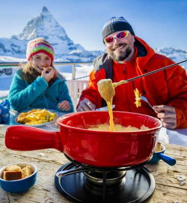 Canvas print Skiers in a restaurant, Fondue, traditional Swiss dish - Matterhorn in Swiss Alps in background