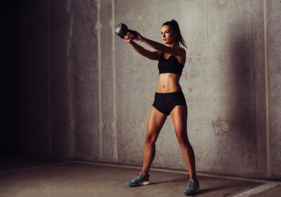 Canvas print Slim attractive sportswoman in a kettlebell training