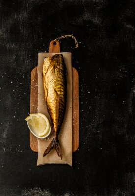 Canvas print Smoked mackerel and lemon slices on black from above